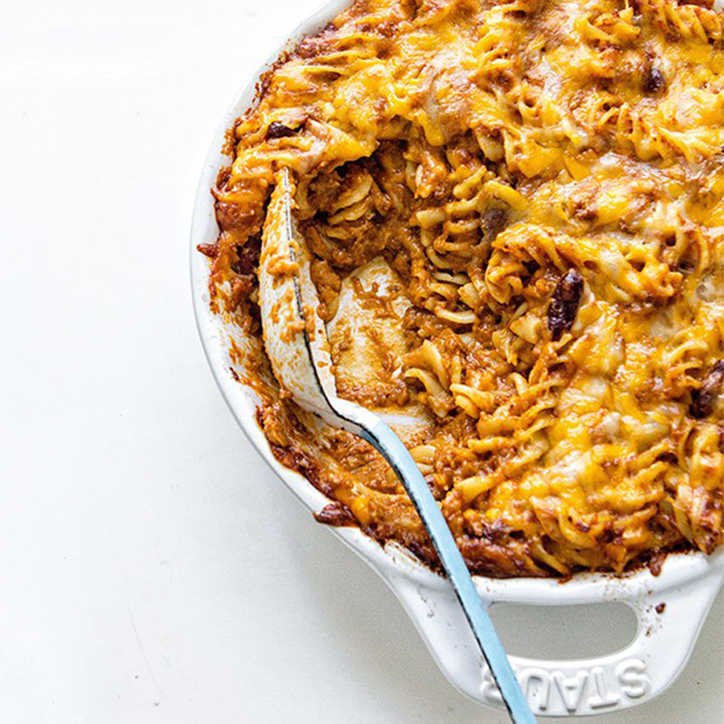 Chili mac and choose in a white dish with a serving spoon.
