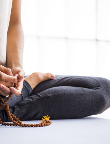 Woman practicing meditation on a mat with a rope.