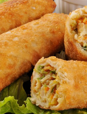 Egg rolls stacked upon one another on celery.