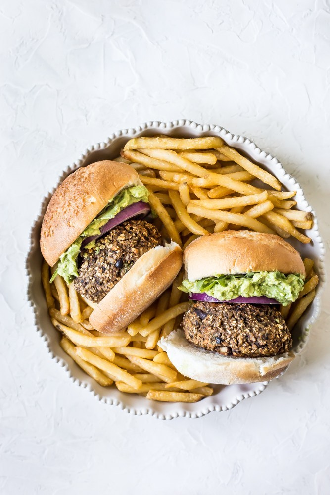 Two burgers with french fries in a dish.