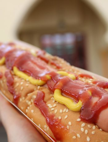 Foot long hot dog being held by someone with ketchup and mustard.