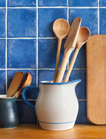 Blue blacksplash design with a cutting board and two utensil holders.