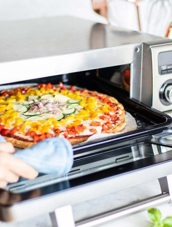 Pizza coming out of a Sharp Supersteam Countertop Oven.