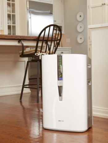 Air purifier on the kitchen floor with a mother and daughter in the background.