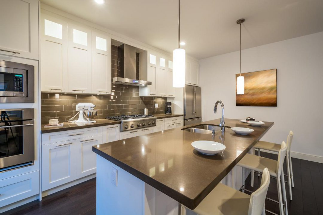 Modern kitchen design with white cabinets and grey subway tile backsplash.