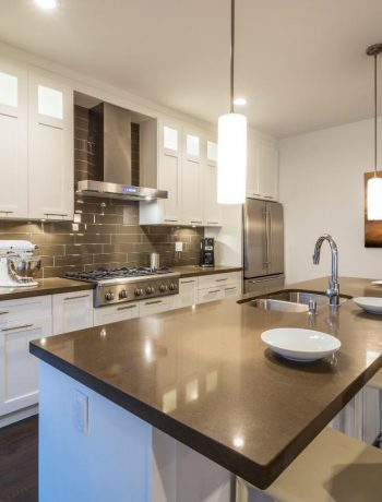 Modern kitchen design with white cabinets and grey subway tile backsplash.