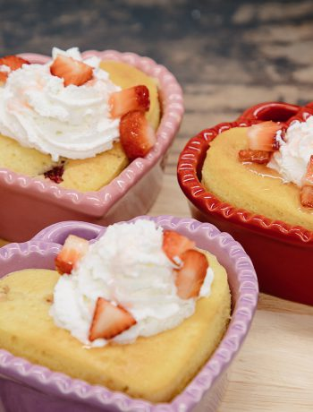 Four heart shaped strawberry shortcakes on a wooden surface.
