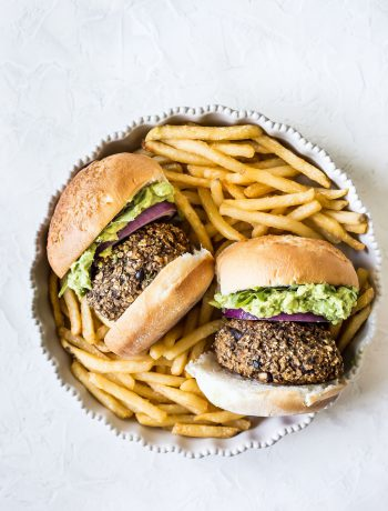 Two sweet potato mushroom burgers and french fries in a dish.