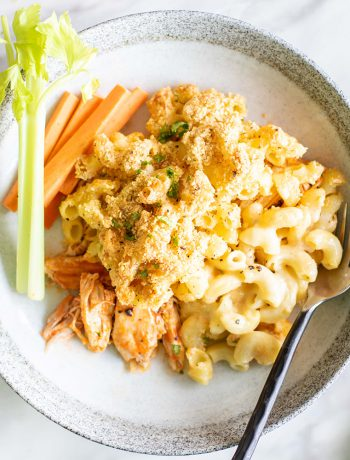 Buffallo mac and cheese with carrots on a plate with a fork.