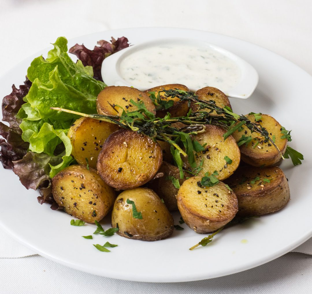 Potatoes on a plate with dipping sauce and lettuce.