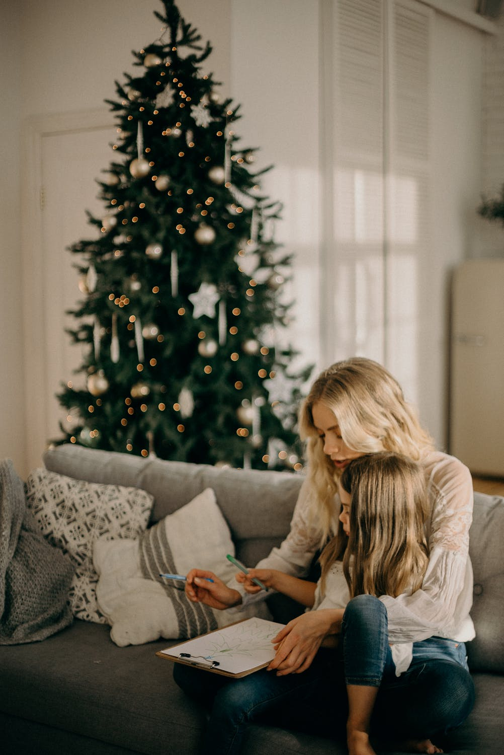 Mother and daughter sitting on a couch with a Christmas tree in the back.