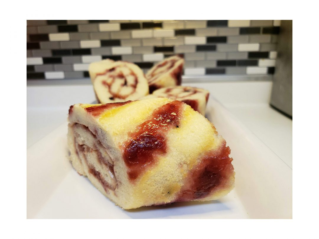 Cherry jam pancake rolls on a tray on a countertop.