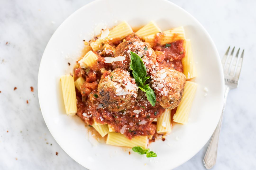 Rigatoni with meatballs in a bowl next to a fork.