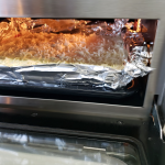 Food cooking in an oven wrapped in tin foil.