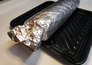 Lasagna wrapped in tin foil on a black tray.