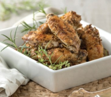 Herbed wings in a square bowl.