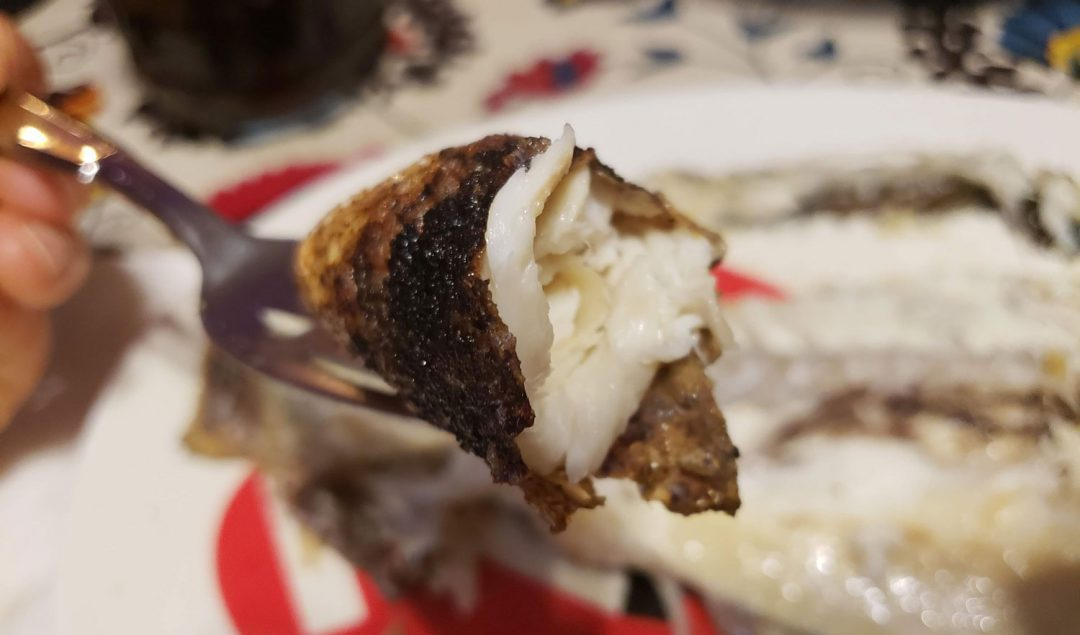 Whole branzino on a fork lifted from a plate.
