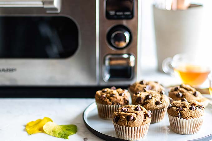 Chocolate muffins with chocolate chips on a plate next to a Sharp Countertop oven.