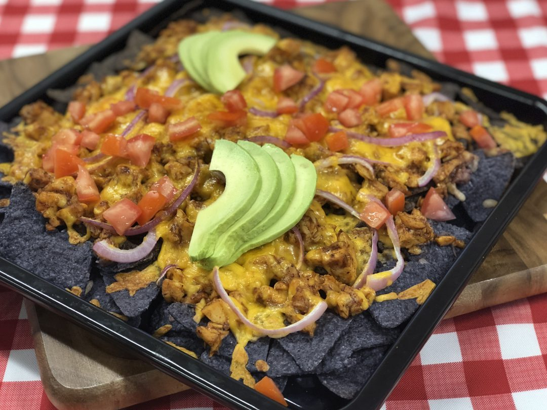 Nachos with topping in a square tin on top of a checkered tablecloth.