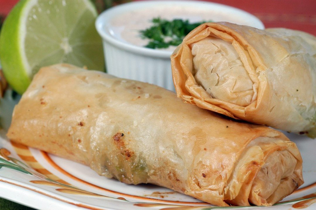 Two chinese egg rolls on a plate.