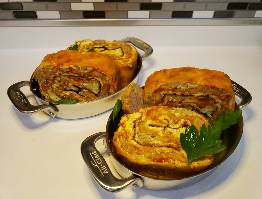 Two lasagna rolls in pots on a countertop.