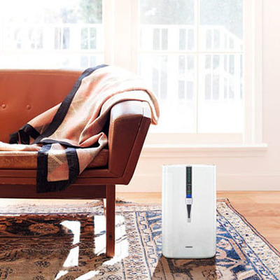 Air humidifier in a living room next ro a couch on a rug.