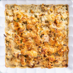 Cauliflower cheese in a square dish on a countertop.