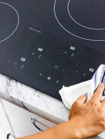 Someone cleaning an induction cooktop with a white rag.
