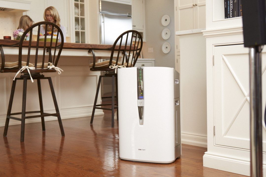 Sharp air purifier on a wooden floor in a kichen near two people.