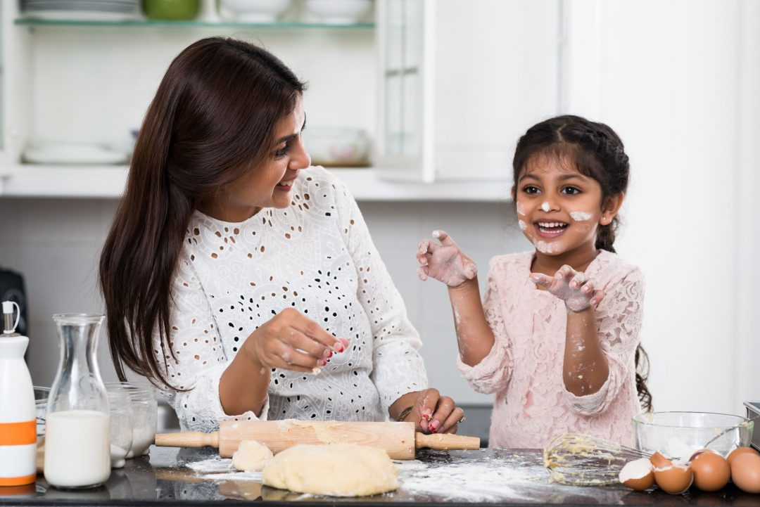 Mother and daughter acting silly while baking