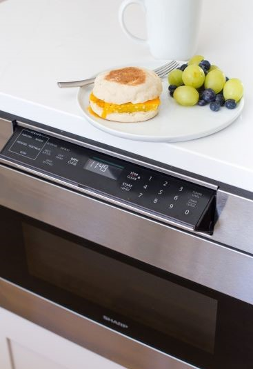 Sharp Microwave drawer underneath a breakfast sandwhich and fruit.