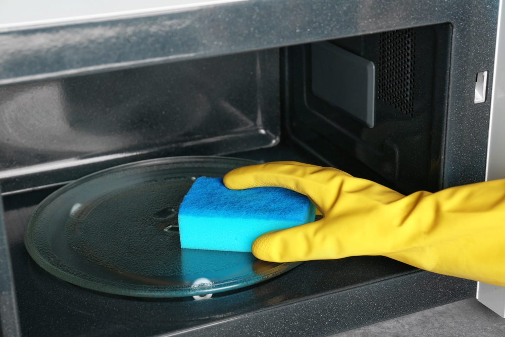 Someone with a blue sponge cleaning the microwave.