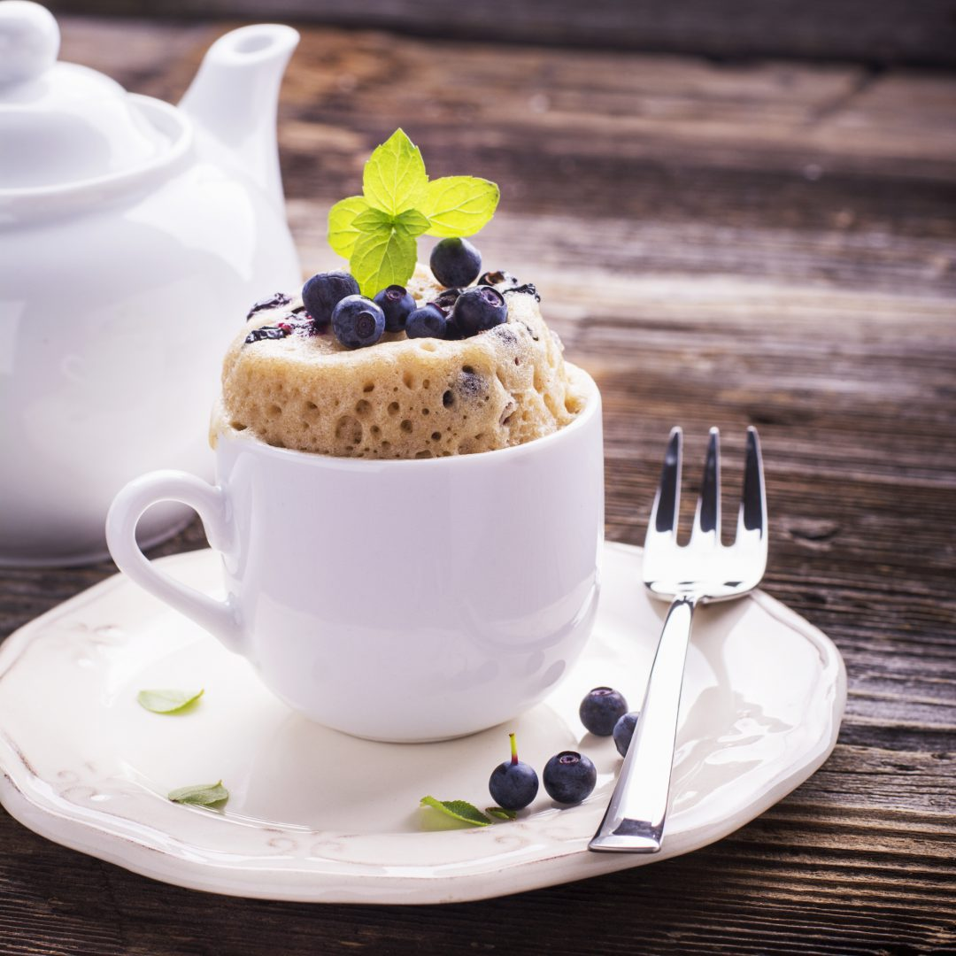 Blueberry mug cake on a plate with a fork.