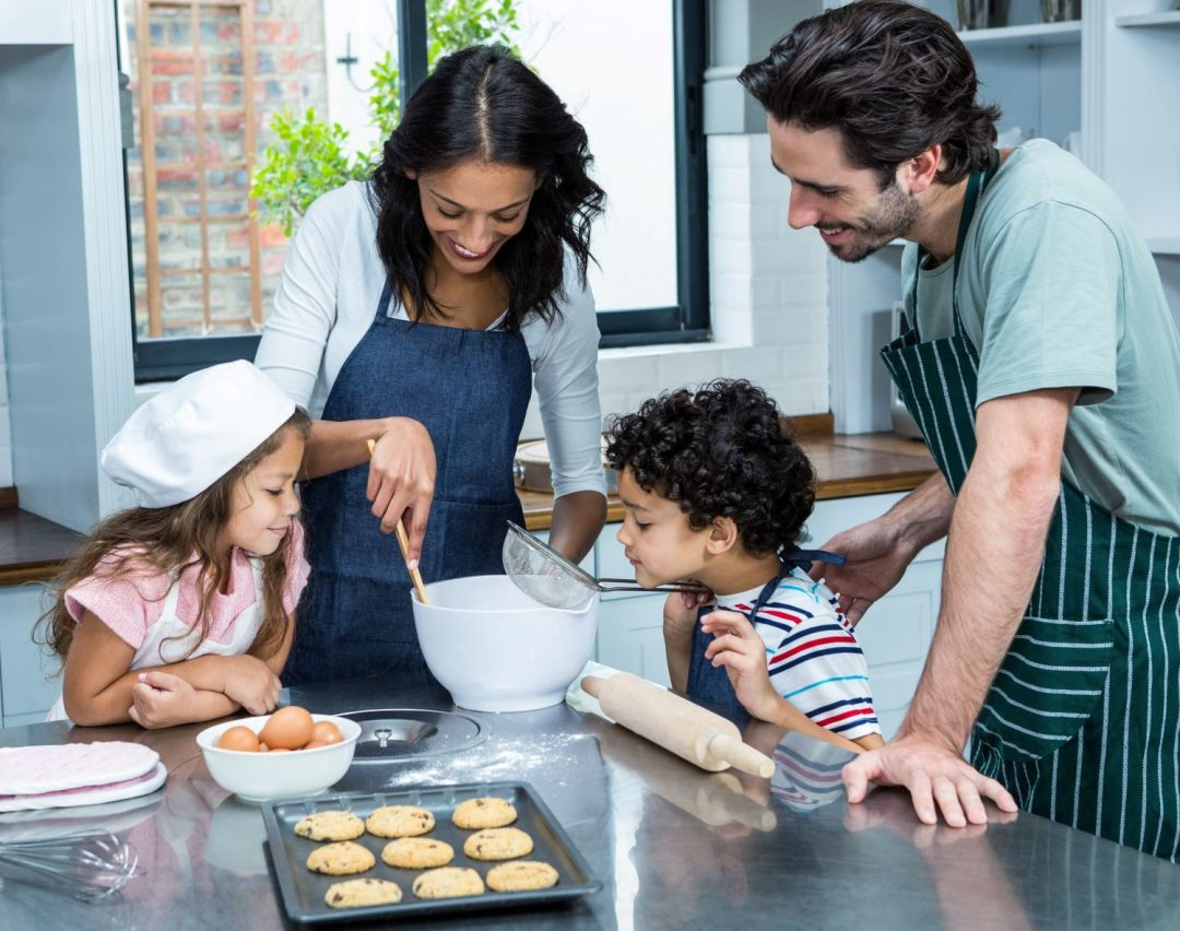 Family of four baking in a kitchen.