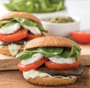 Two portobello burger on a butcher block and plate.