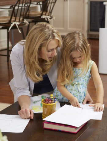 Mother and daughter coloring in a living room near air purifier.