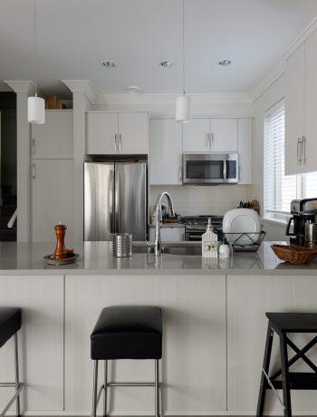 White kitchen design with three black stools.