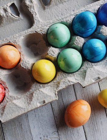 Dyed colored eggs in a carton.