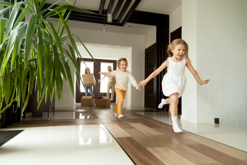 Family with children running down a hallway.