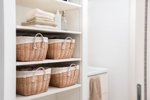Laundry baskets on shelves in a laundry room.