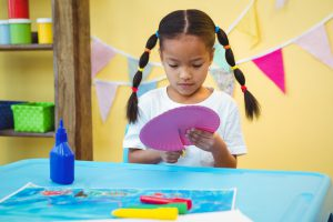 Young girl cutting and coloring paper plate.