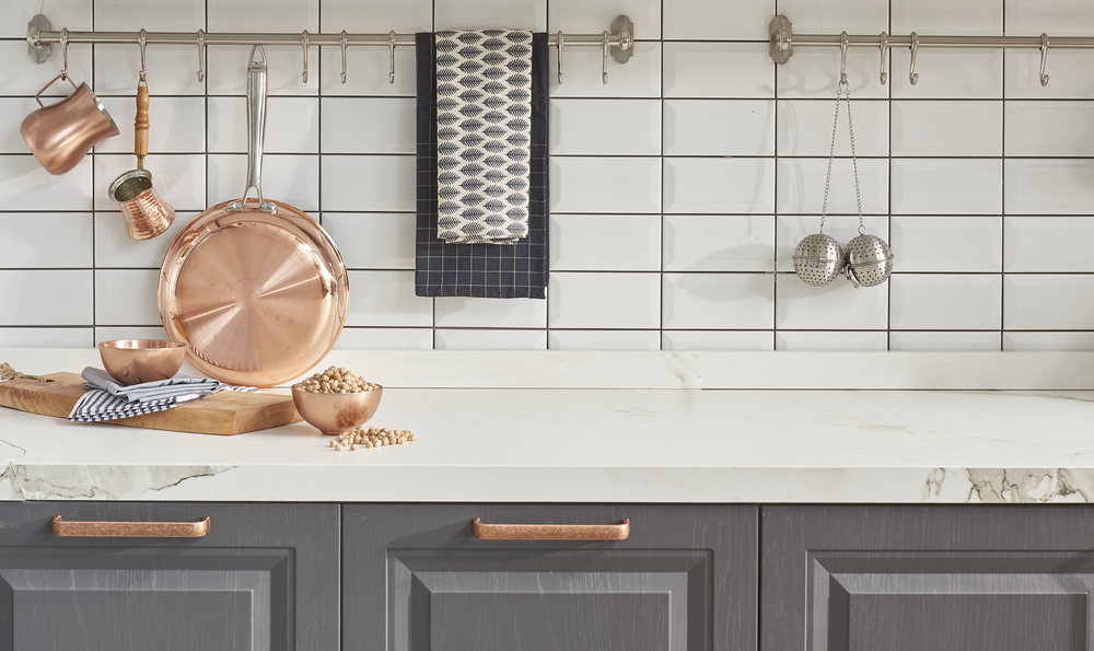 Pots, pans, and kitchen accessories on top of a counter and cabinets.