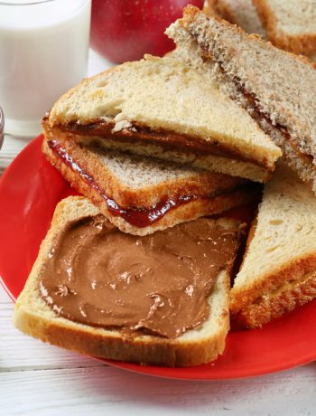 Peanut butter and jelly sandwiches sitting on a plate.