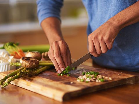 Chopping greens on a cutting board.