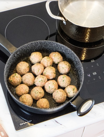 Meatballs cooking on an induction cooktop.