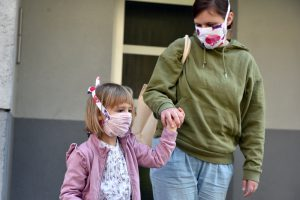 Mother and daughter wearing face mask outdoors.