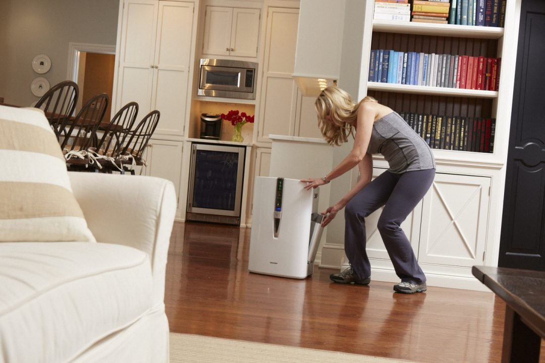 Woman adjusting air purifier in her home.