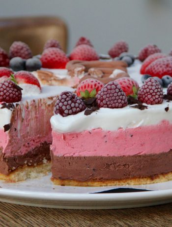 Three layered ice cream cake with strawberries on top.