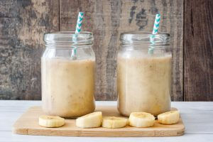 Two banana smoothies on a wooden tray.