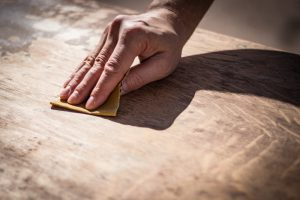 Someone using sandpaper to smoothen a flat surface,